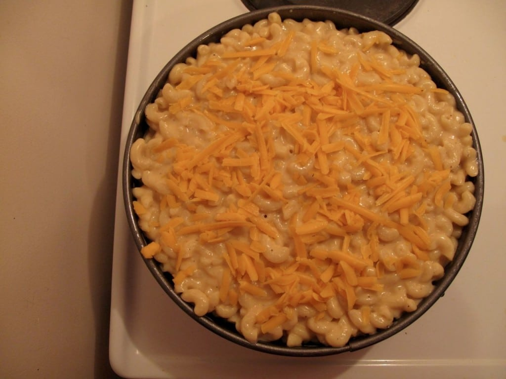Spoon the remainder of mac and cheese over pulled pork and sprinkle with more cheddar.