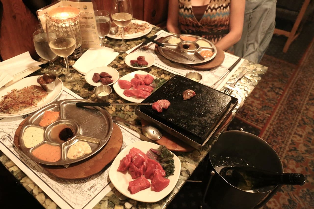 Sear raw beef on a hot stone then dip in Grizzly House Banff's special sauces.