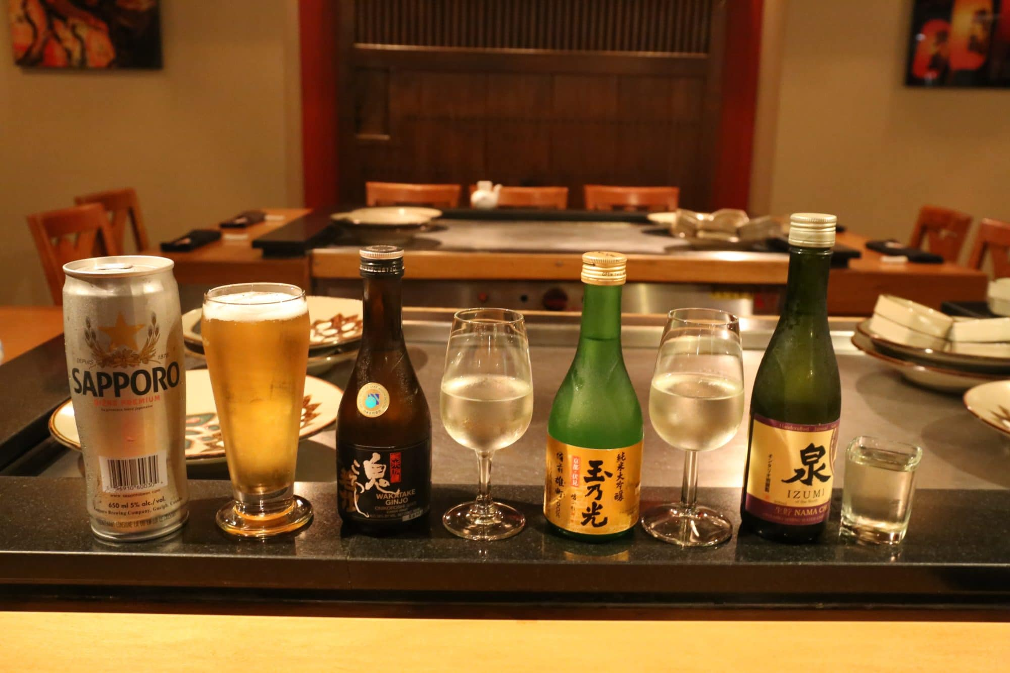 "Japanese Drink Sampling left to right | sapporo, izumi ""namo cho"" sake, wakatake onikoroshi ginjo, tamanohikari junmai dai-ginjo"