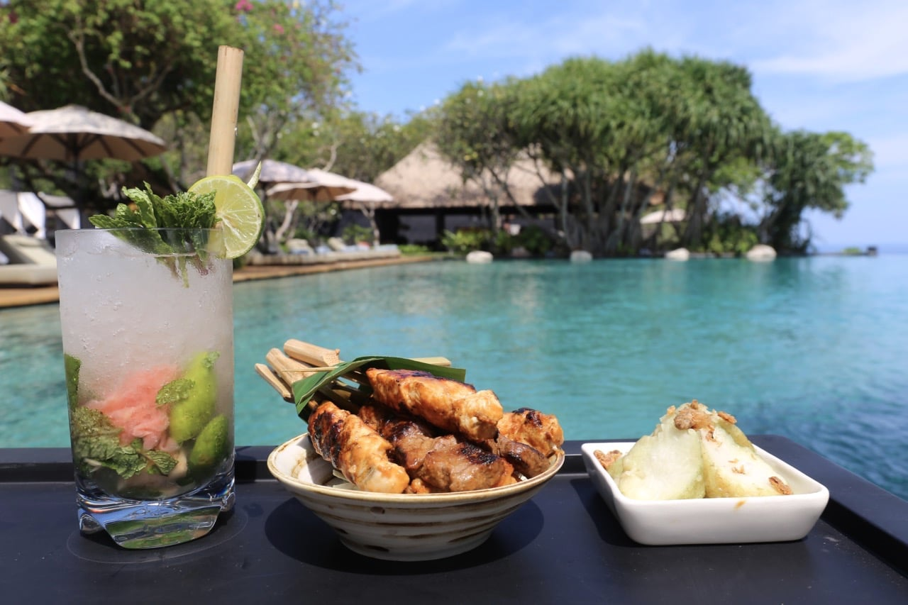 Enjoy a cocktail and Balinese snack by the hotel's infinity pool.