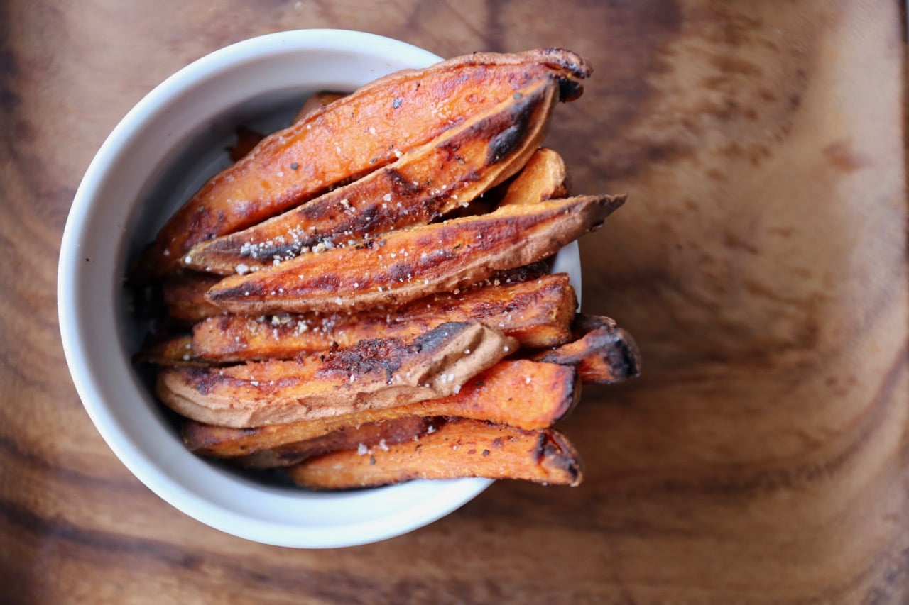 Best Oven Baked Sweet Potato Fries Tips tossed in salt and pepper and served with dipping sauce.