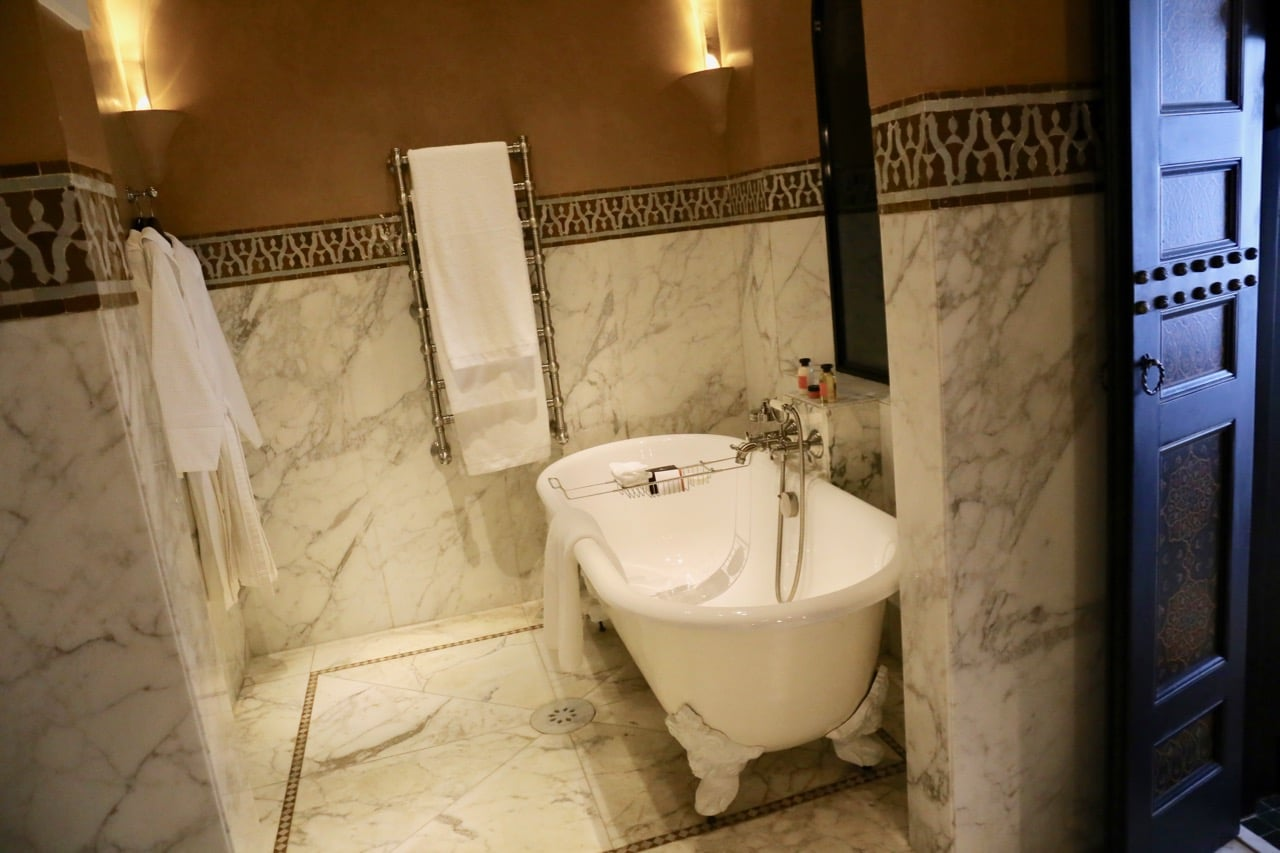 Enjoy a relaxing bubble bath in a white marble adorned suite.