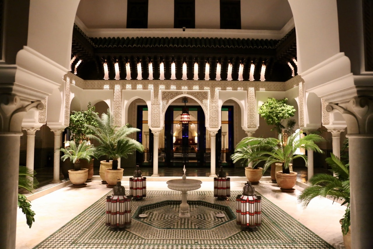 A romantic open-air courtyard glows within La Mamounia Hotel at night.