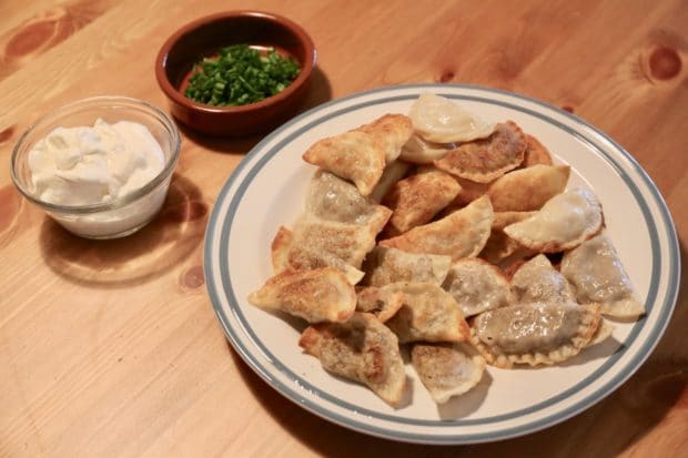 After boiling homemade pierogies fry in oil and serve with sour cream and chives.