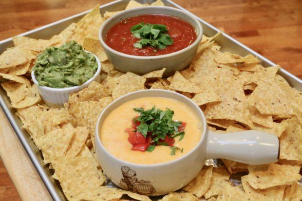 Classic Velveeta Cheese Dip served with nachos, salsa and guacamole.