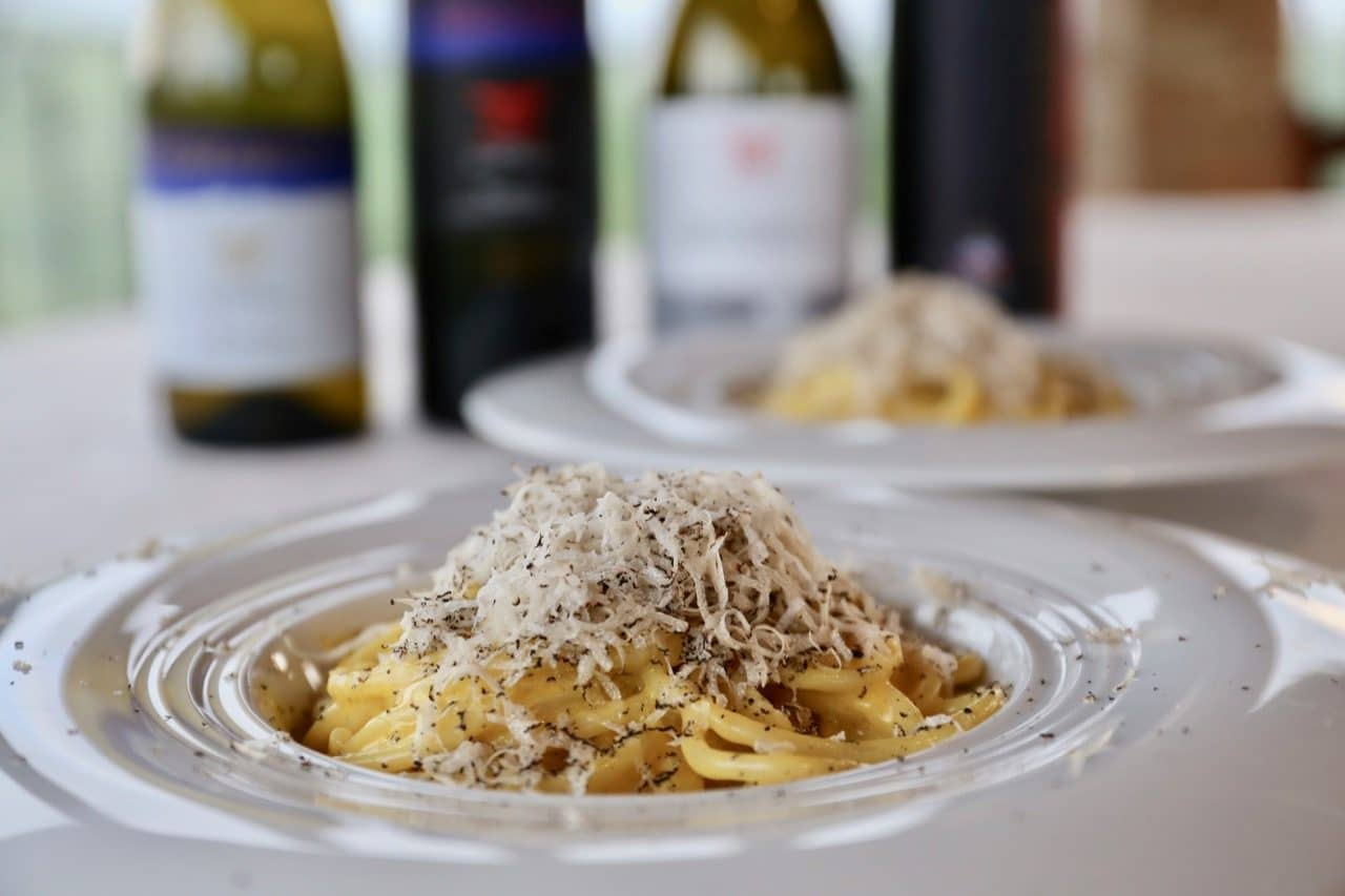 A famous Italian chef serves pici pasta topped with shaved black truffle in Volterra.