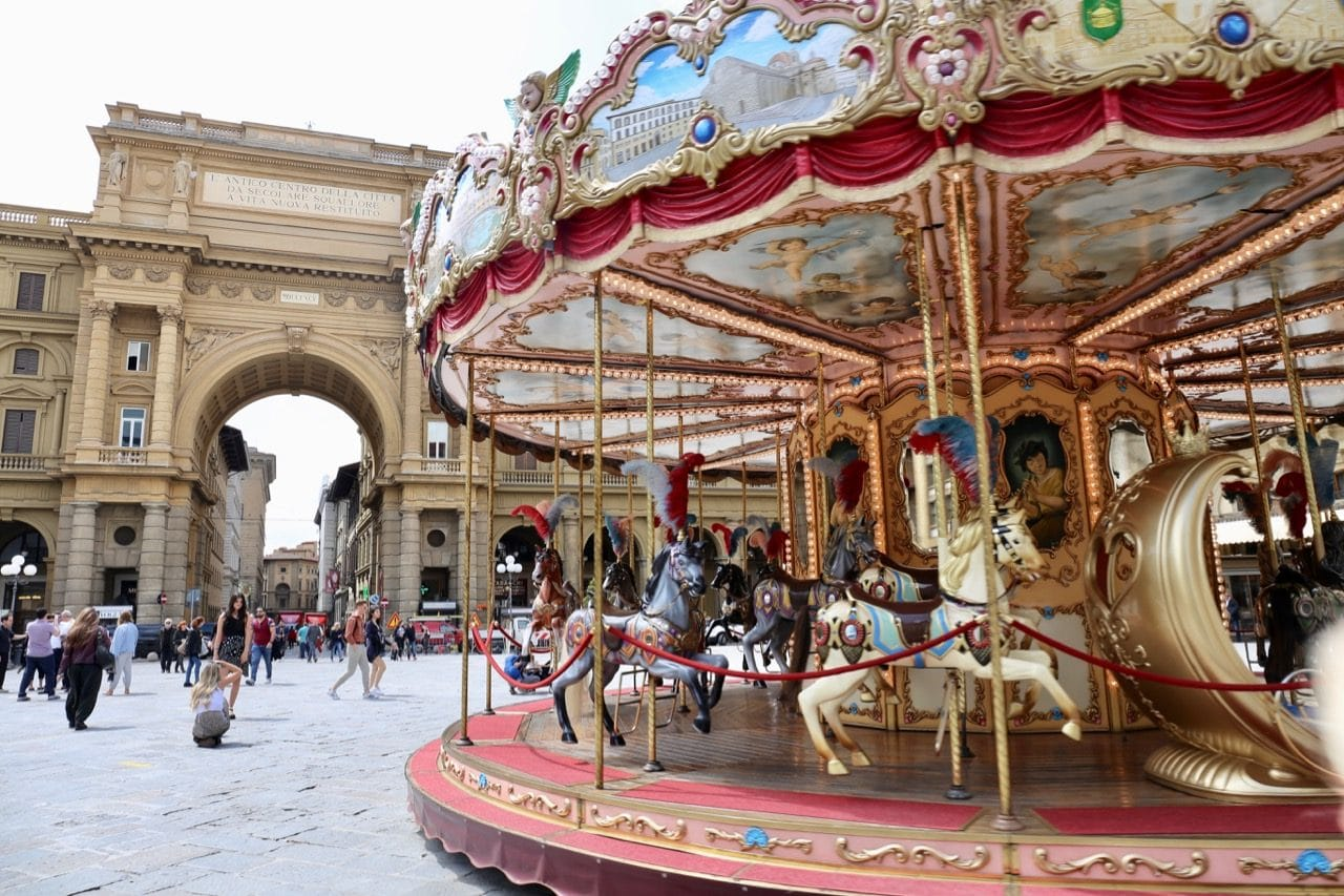 A vintage carousel delights children and families at Piazza della Repubblica.