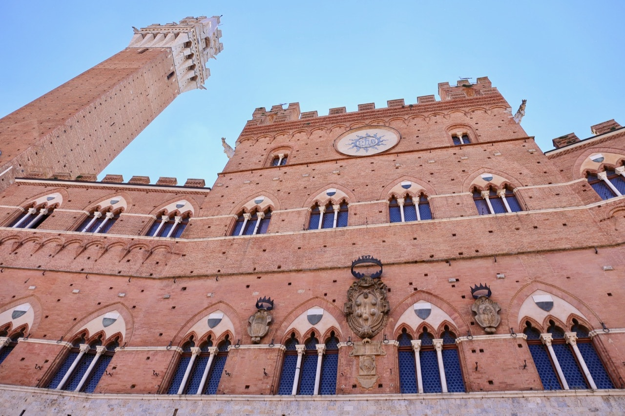Look up and marvel at the architectural beauty of Siena's iconic Palazzo Pubblico.