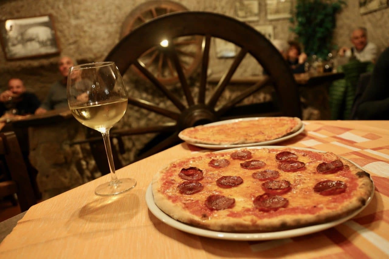 Sip local Tuscan wine while enjoying a pizza feast in Pitigliano.
