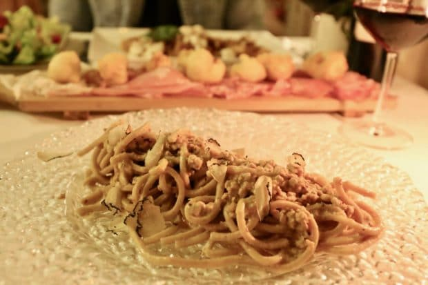 Pici pasta is served with wild boar ragu and black truffles in Pisa.