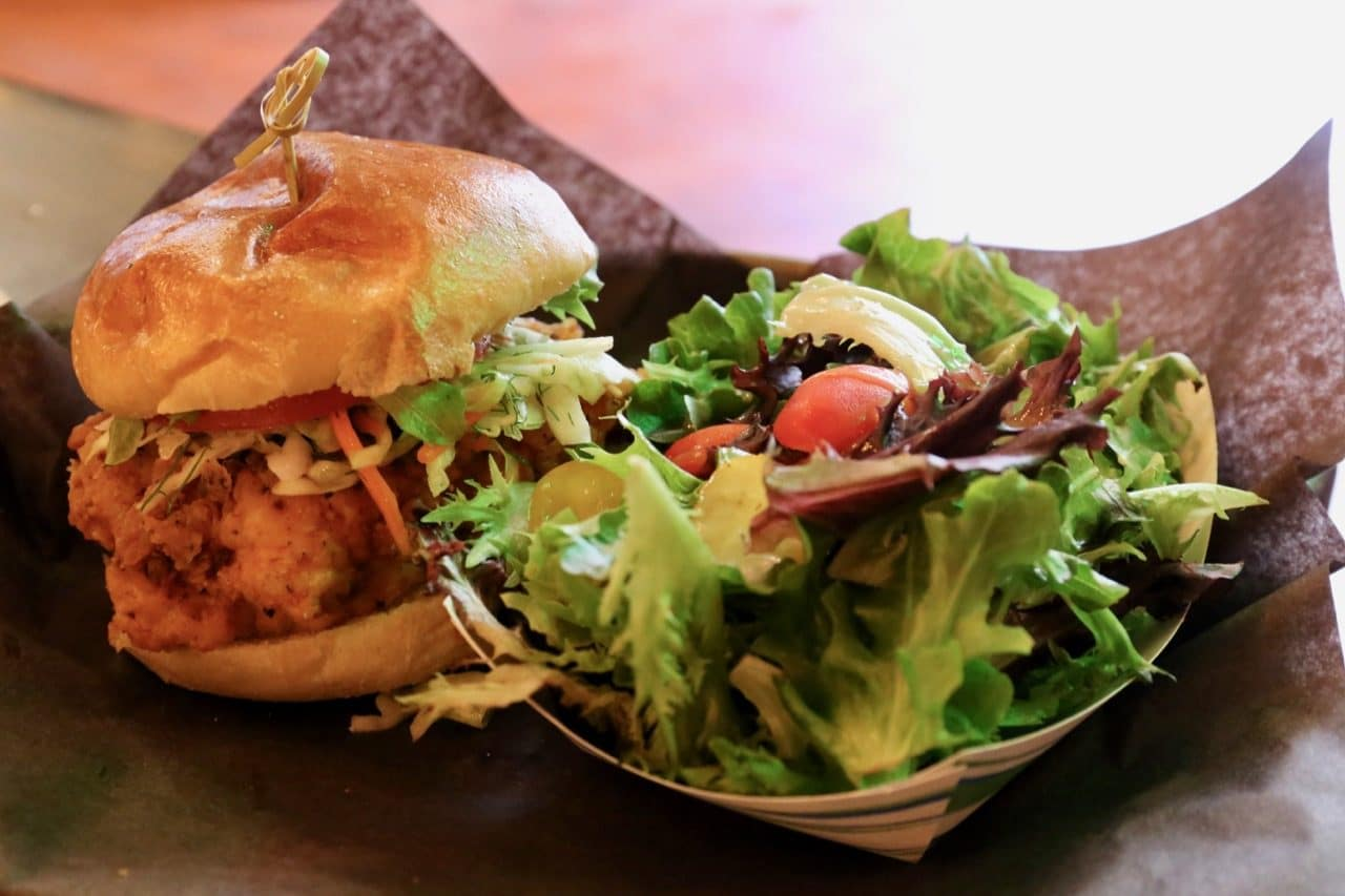 The Yardbird is a fried chicken sandwich served with a fresh seasonal salad.