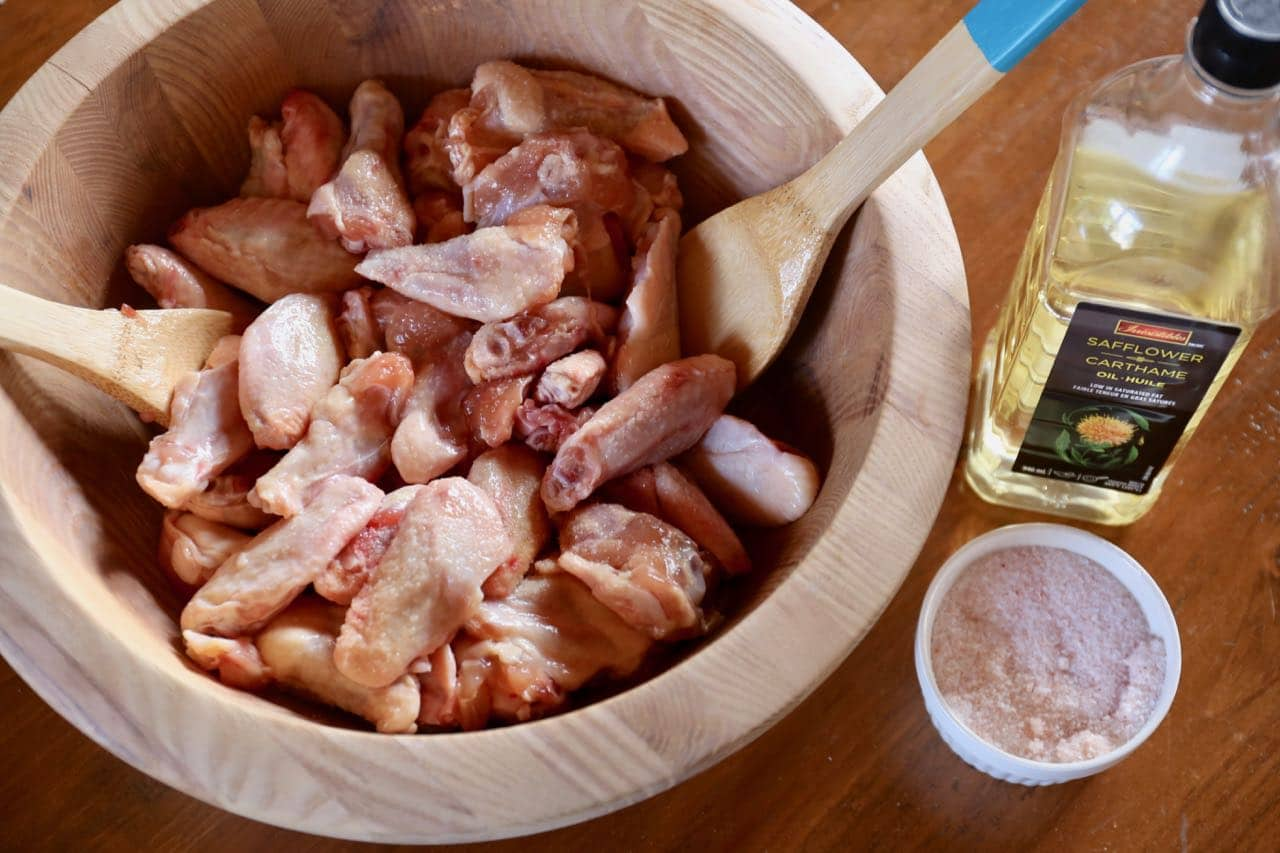 Toss fresh chicken wings in vegetable oil and salt.