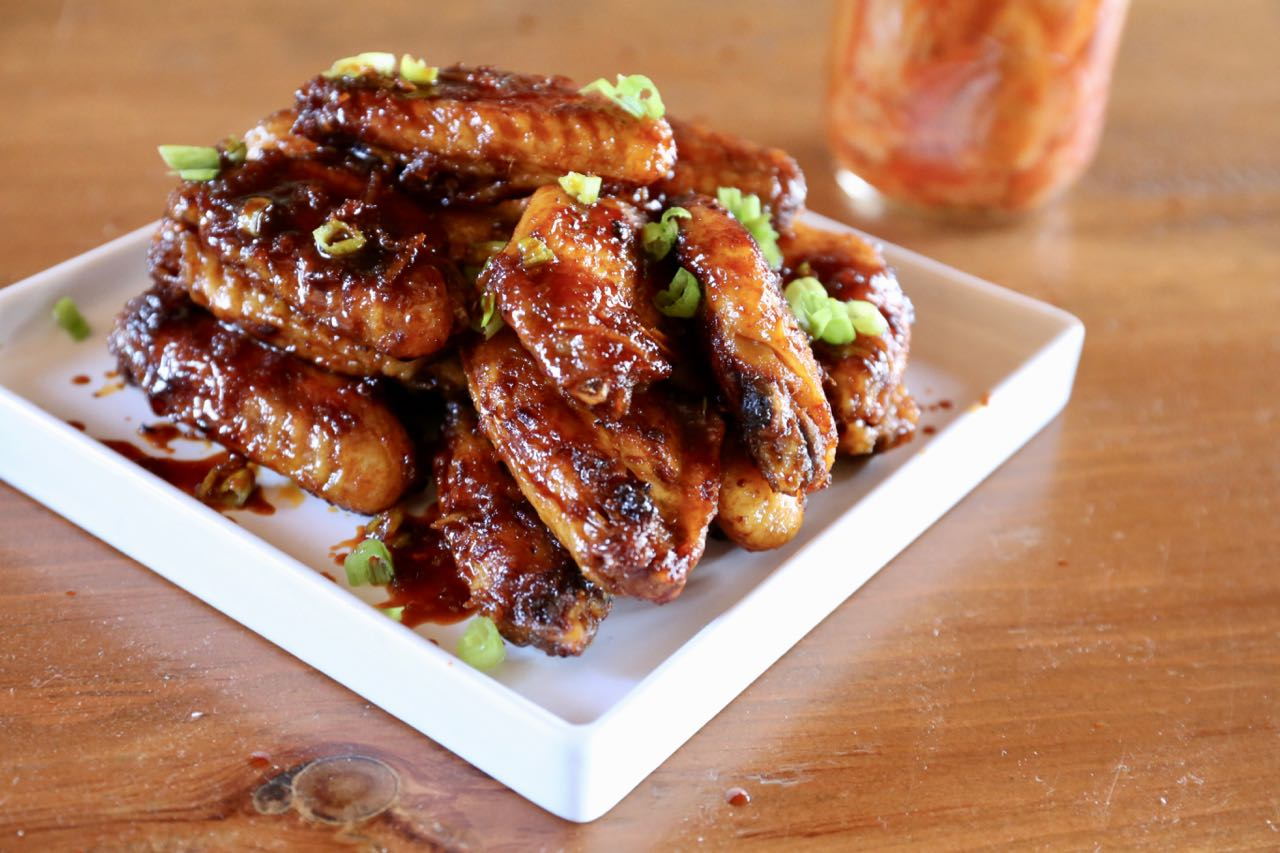 Baked Gochujang chicken wings served topped with green onions.