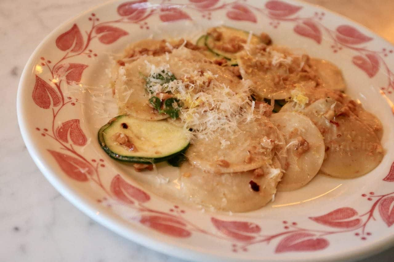 Corzetti are served with walnuts, zucchini and parmesan.