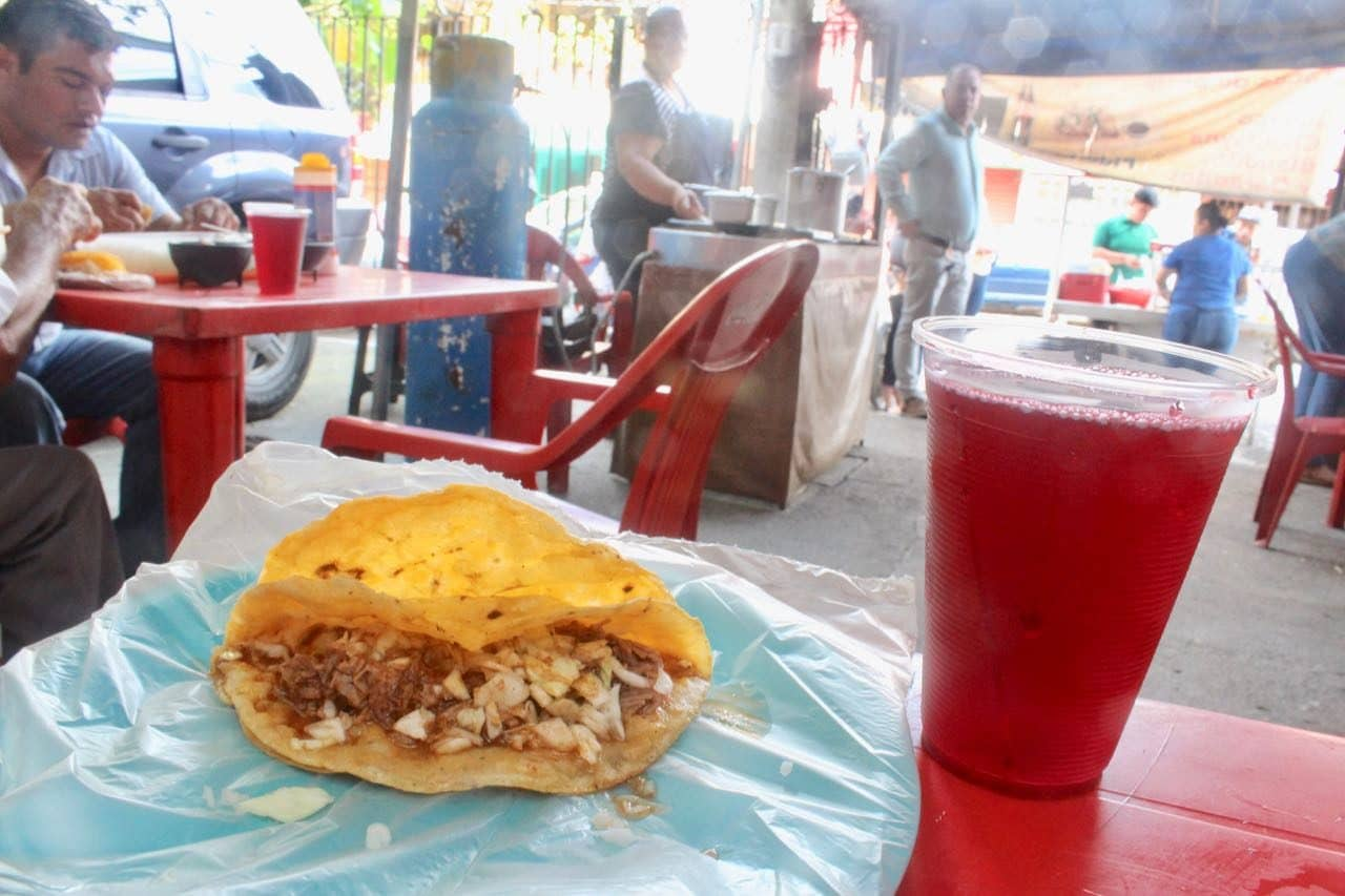 Enjoying a beef taco at Birria Chanfay with glass of hibiscus agaua fresca.