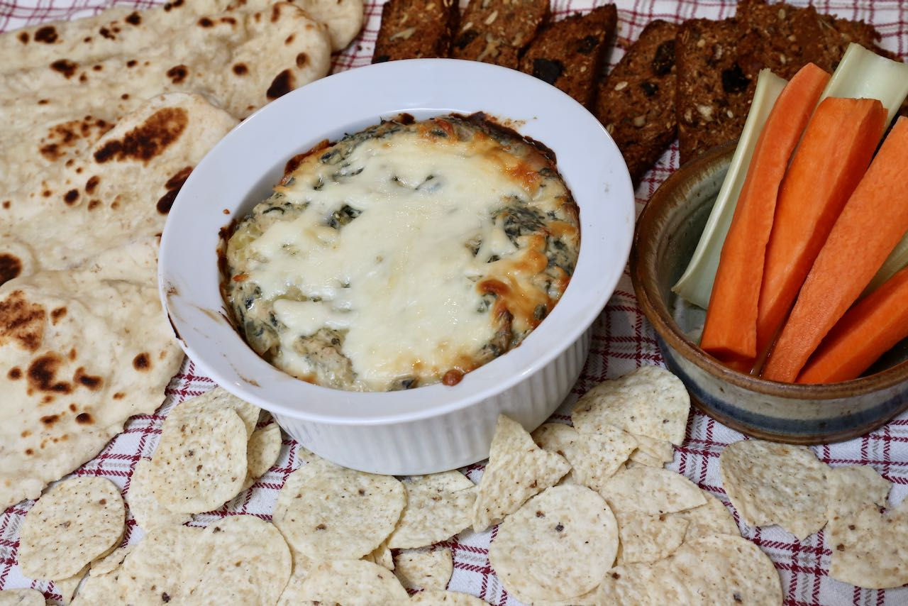 Serve Keto Spinach Dip with nachos, flatbread, crackers and carrot sticks.