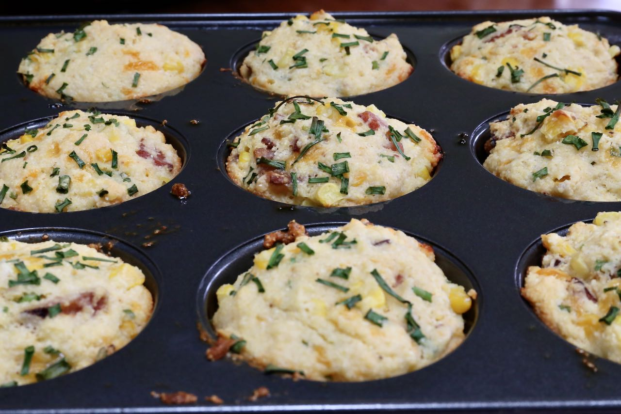 Perfectly browned muffins out of the oven feature sliced chives on top.