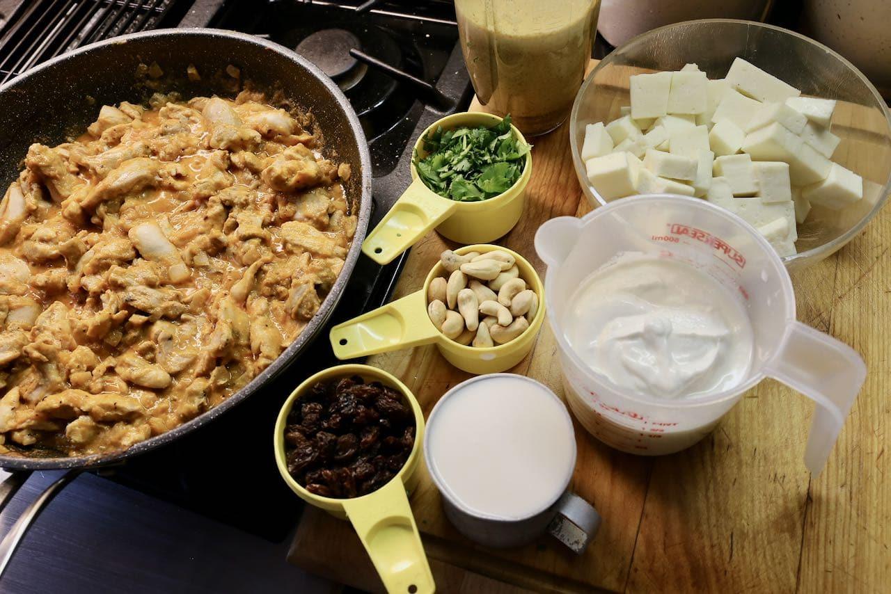 Finish the Shahi Korma recipe by adding raisins, cashews, cilantro, yogurt, cream and paneer.