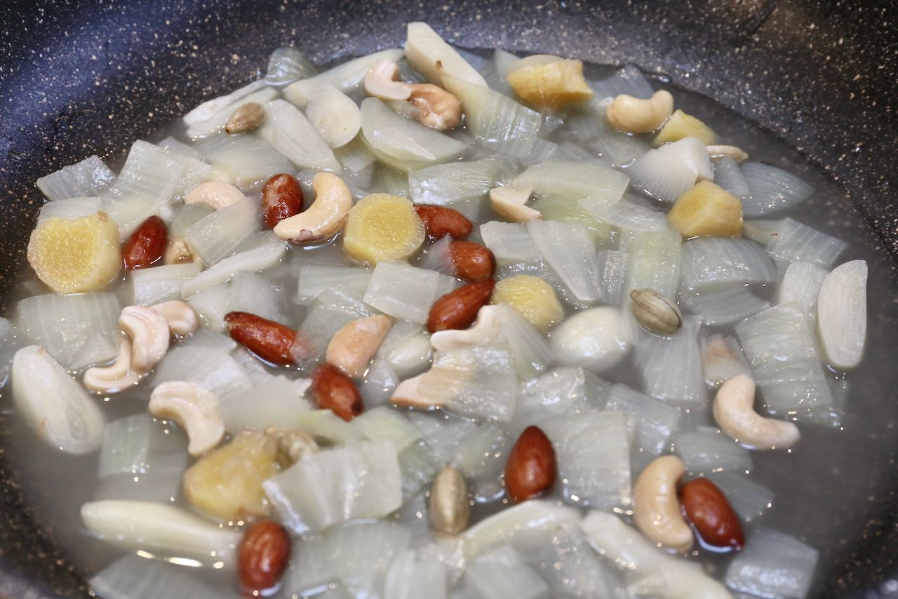 Begin preparing our Shahi Paneer recipe by cooking almonds, cashews, onion and cardamom in water.
