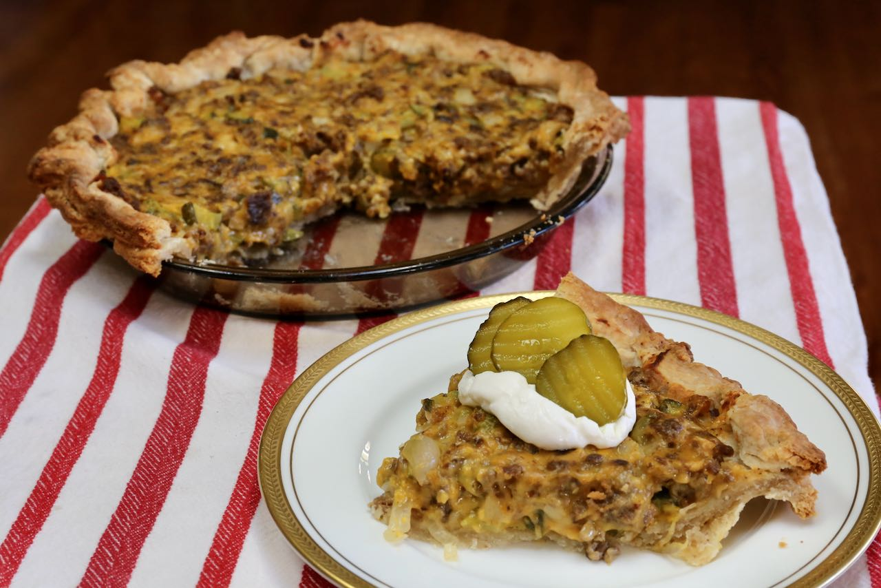 Serve a warm slice of Pickle Pie with dollop of sour cream and sliced pickles.