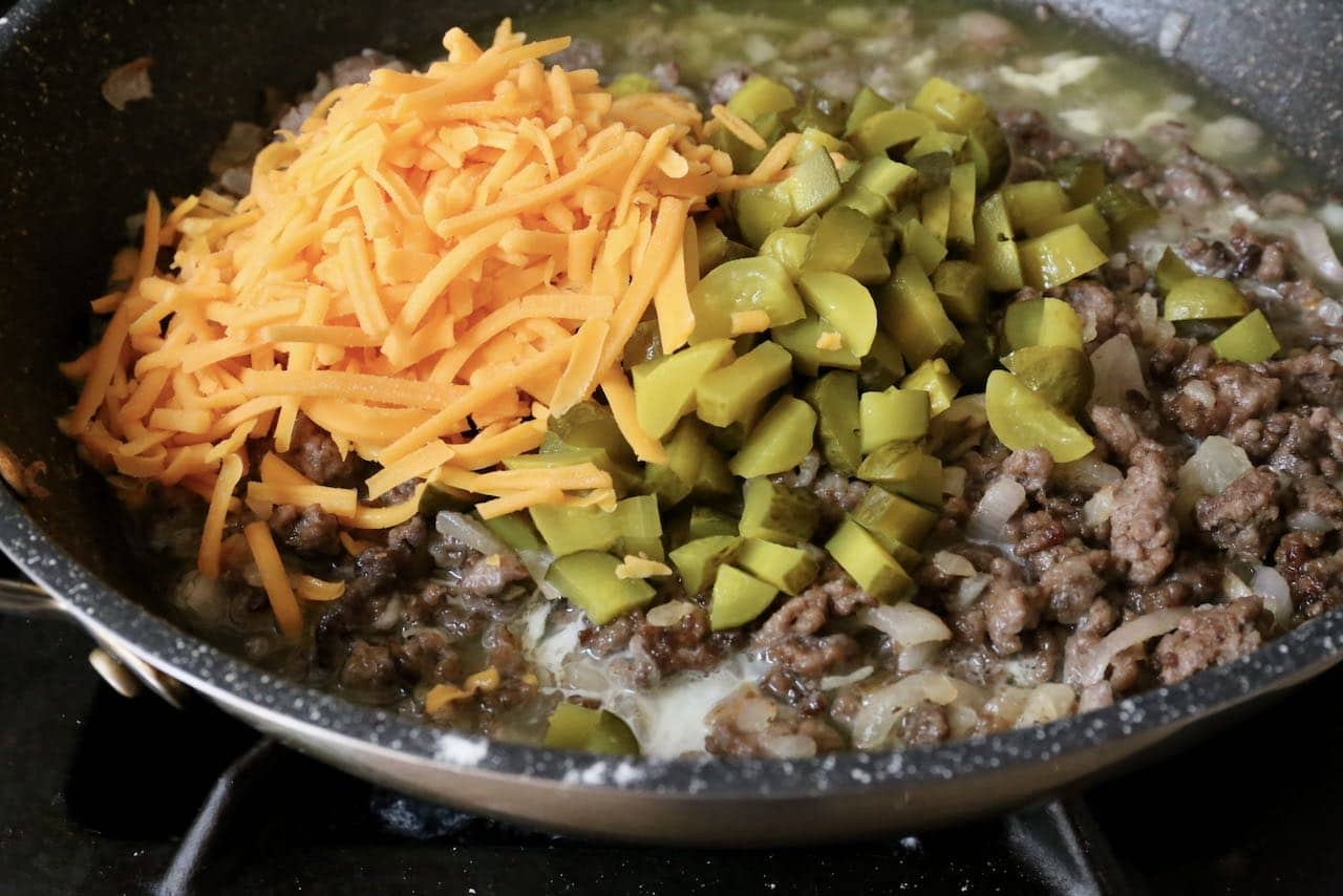 Add shredded cheddar cheese and chopped pickles to browned beef mixture.