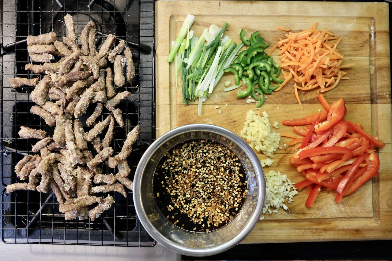 Prepare Calgary Ginger Beef sauce by slicing green onions, peppers, carrots, ginger and garlic.