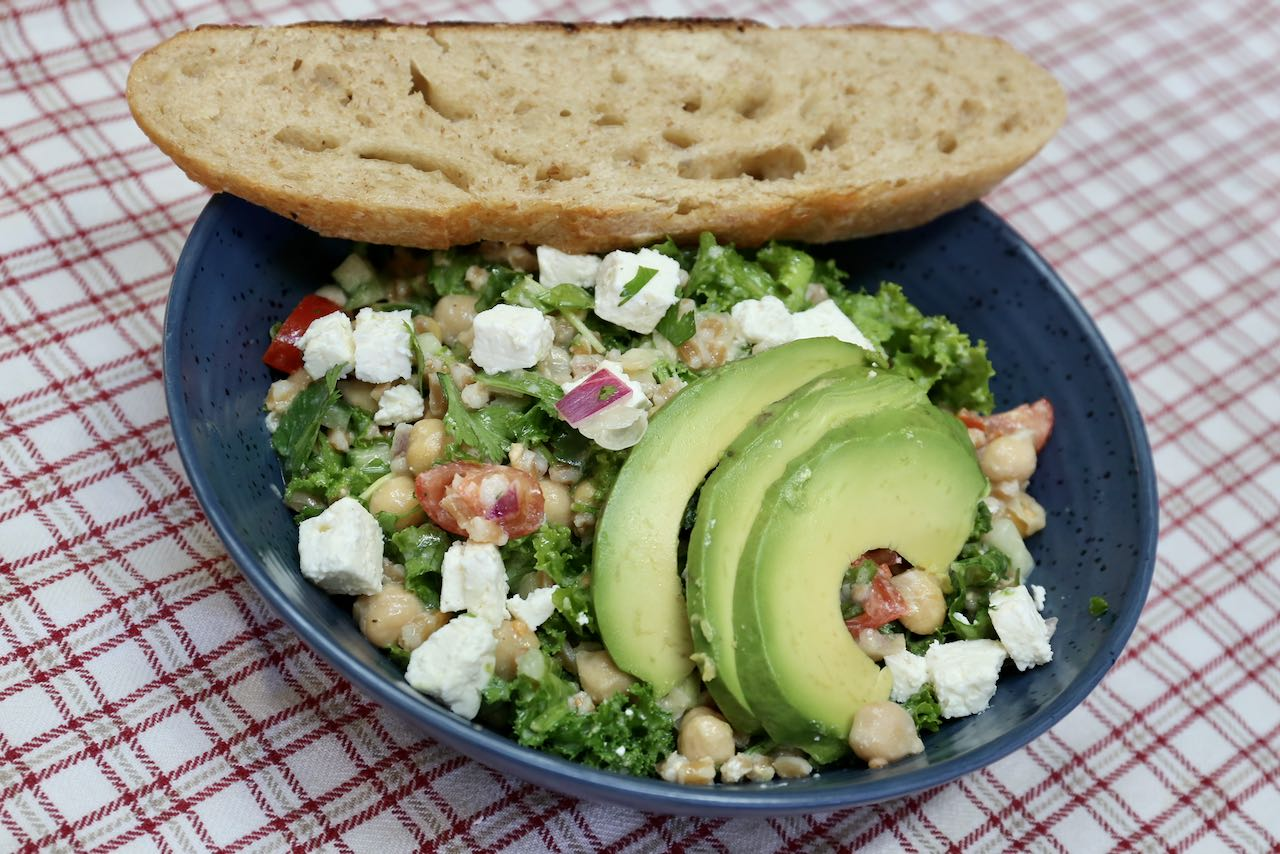 Enjoy Chickpea Avocado Salad sprinkled with feta and a slice of fresh sourdough bread.