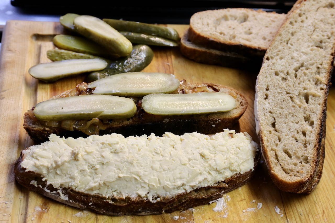 Schmear cheese mixture one one bread slice and caramelized onions and pickles on another.