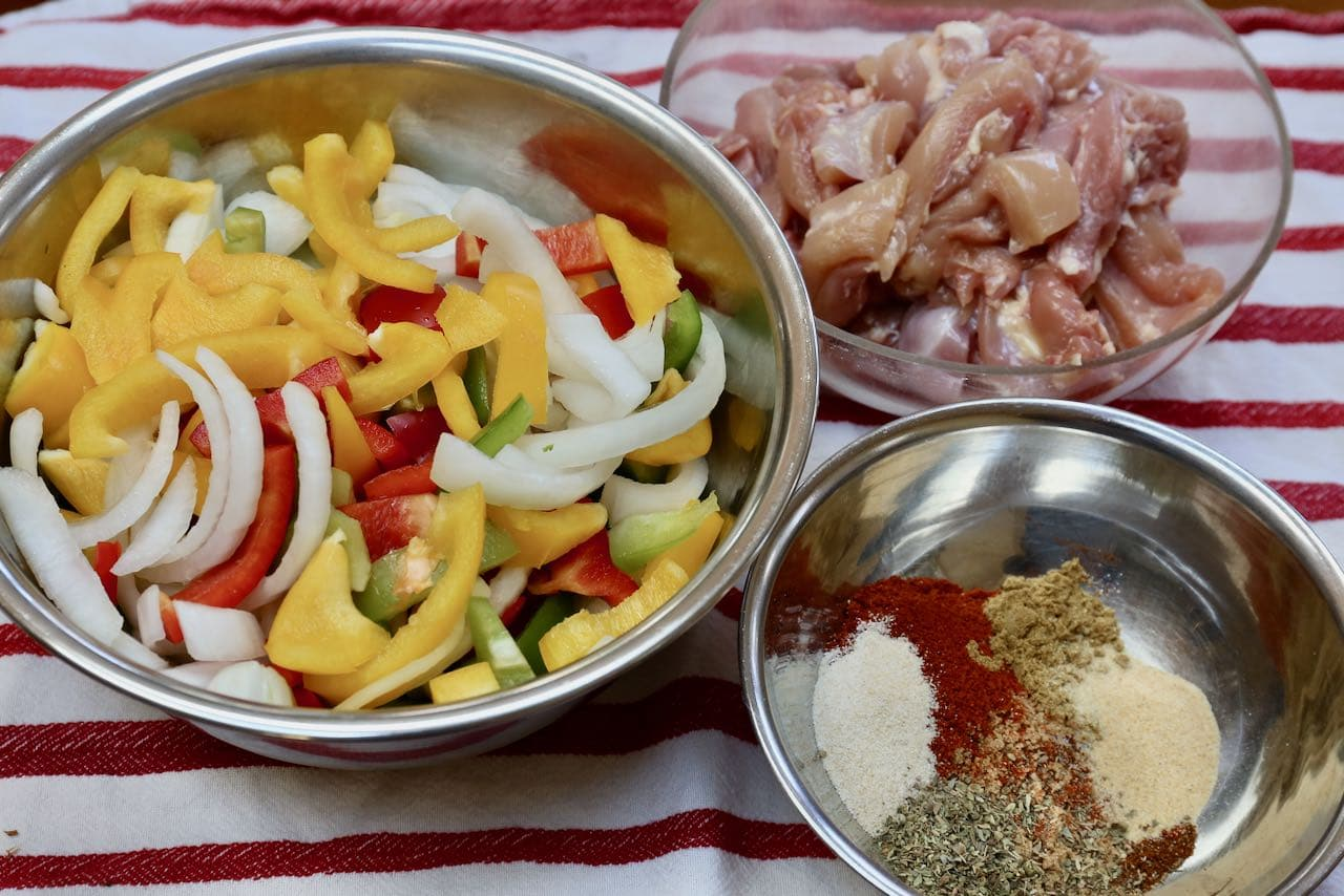 Prepare Fajita Tacos in 3 separate bowls: spice marinade, chicken thighs and sliced vegetables.