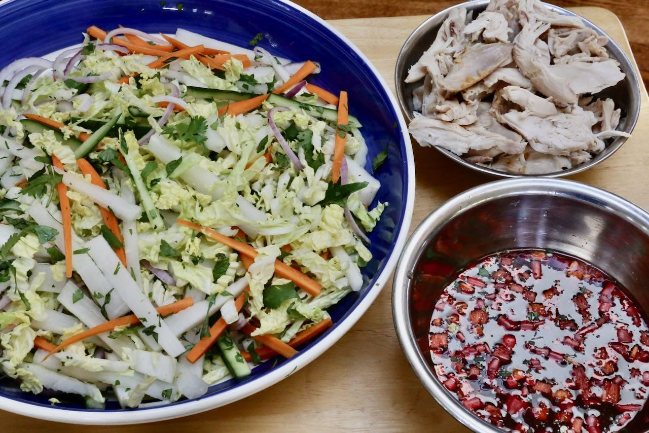 Prepare chopped vegetables, vinaigrette and shredded roast chicken in separate mixing bowls.