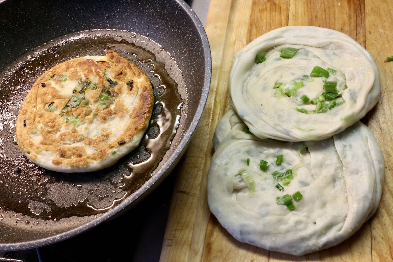 Flip scallion pancakes after frying in oil for 2-3 minutes until golden brown.