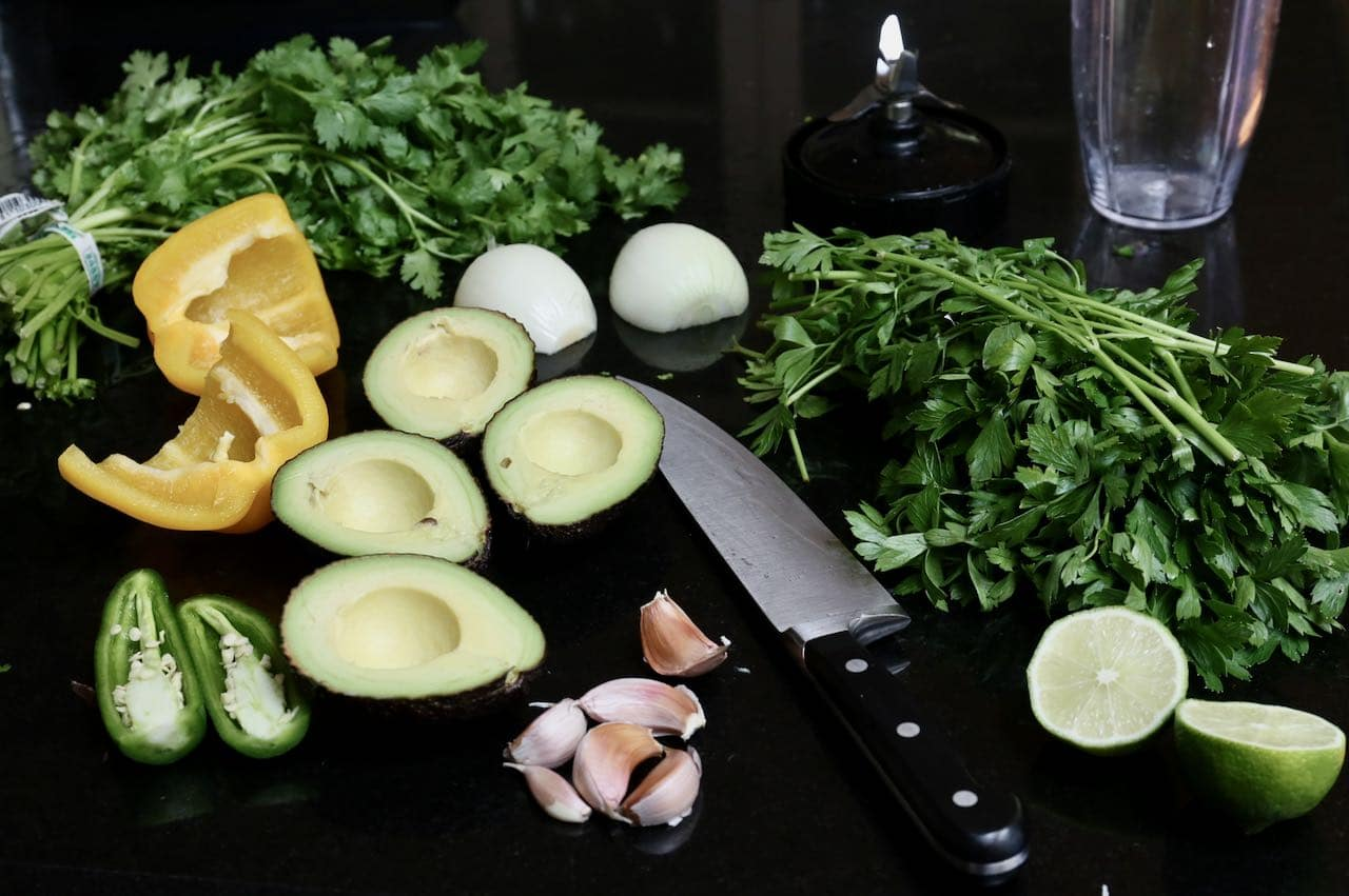Prepare Guasacaca ingredients by chopping into small pieces and placing in a food processor.