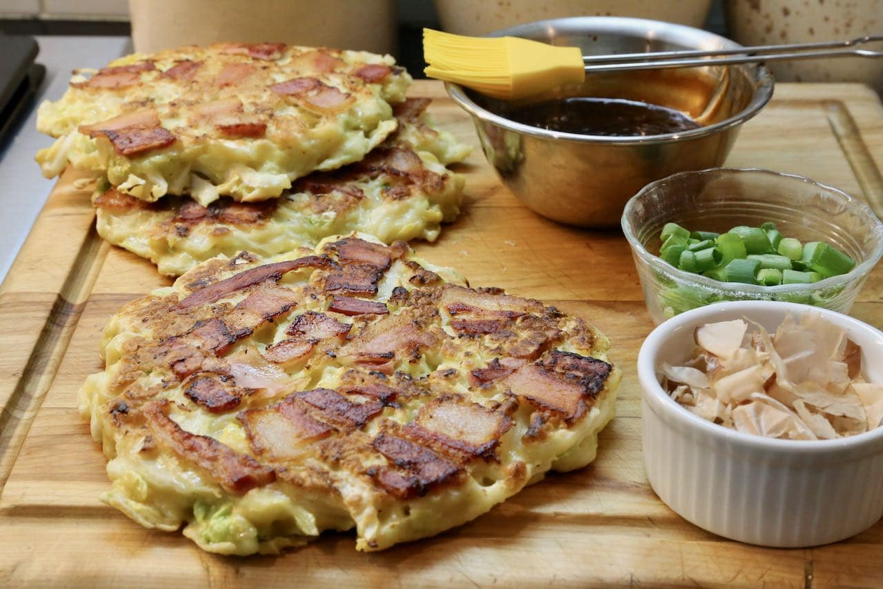 Top Japanese Cabbage Pancake with okonomi sauce, scallions, kewpi mayo and bonito flakes.