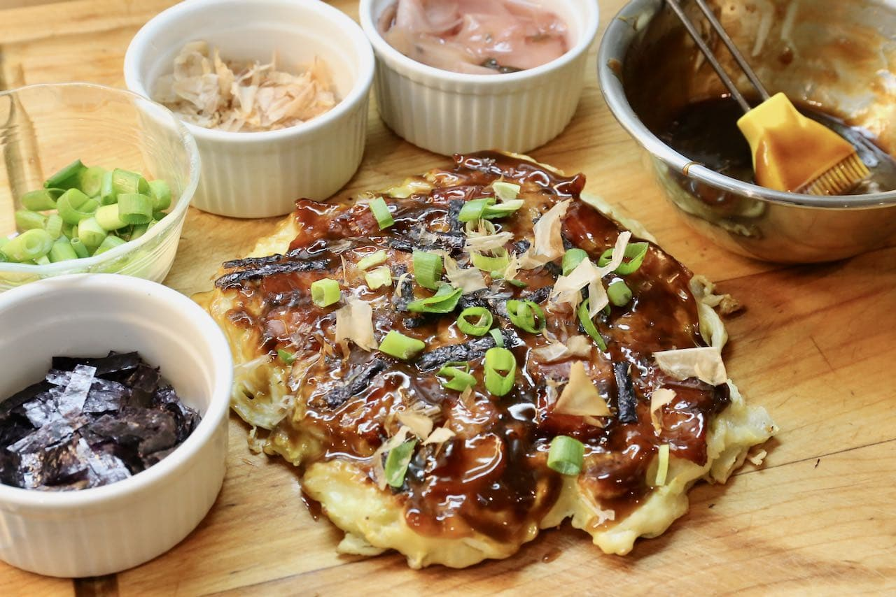 Use a brush to slather homemade okonomi sauce on crispy bacon Japanese pancakes.