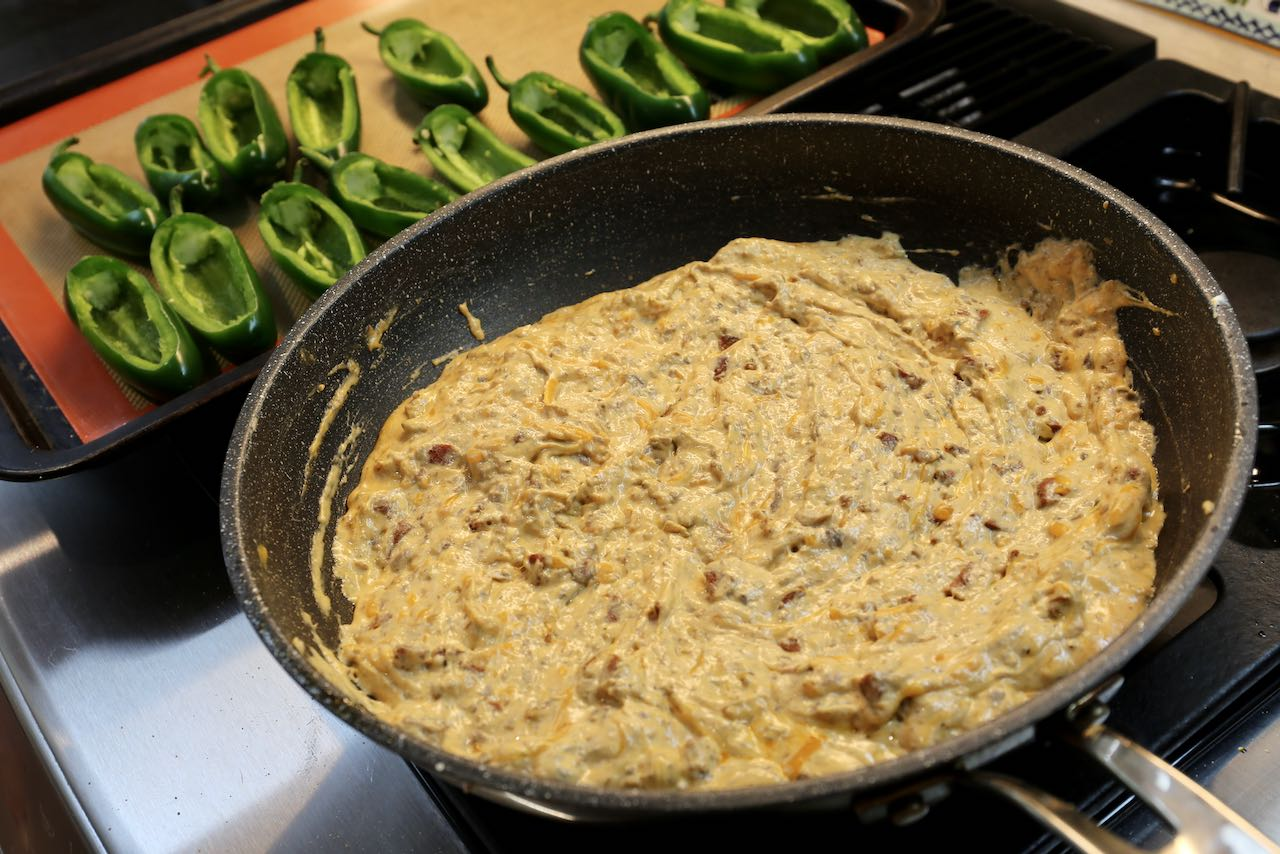 Melt cheesy chorizo filling in a skillet until well combined then scoop into jalapeno pepper boats.