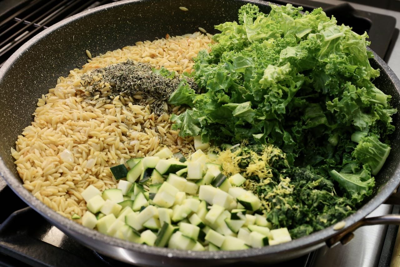 Simmer orzo with vegetables, herbs an lemon zest until just before al dente.