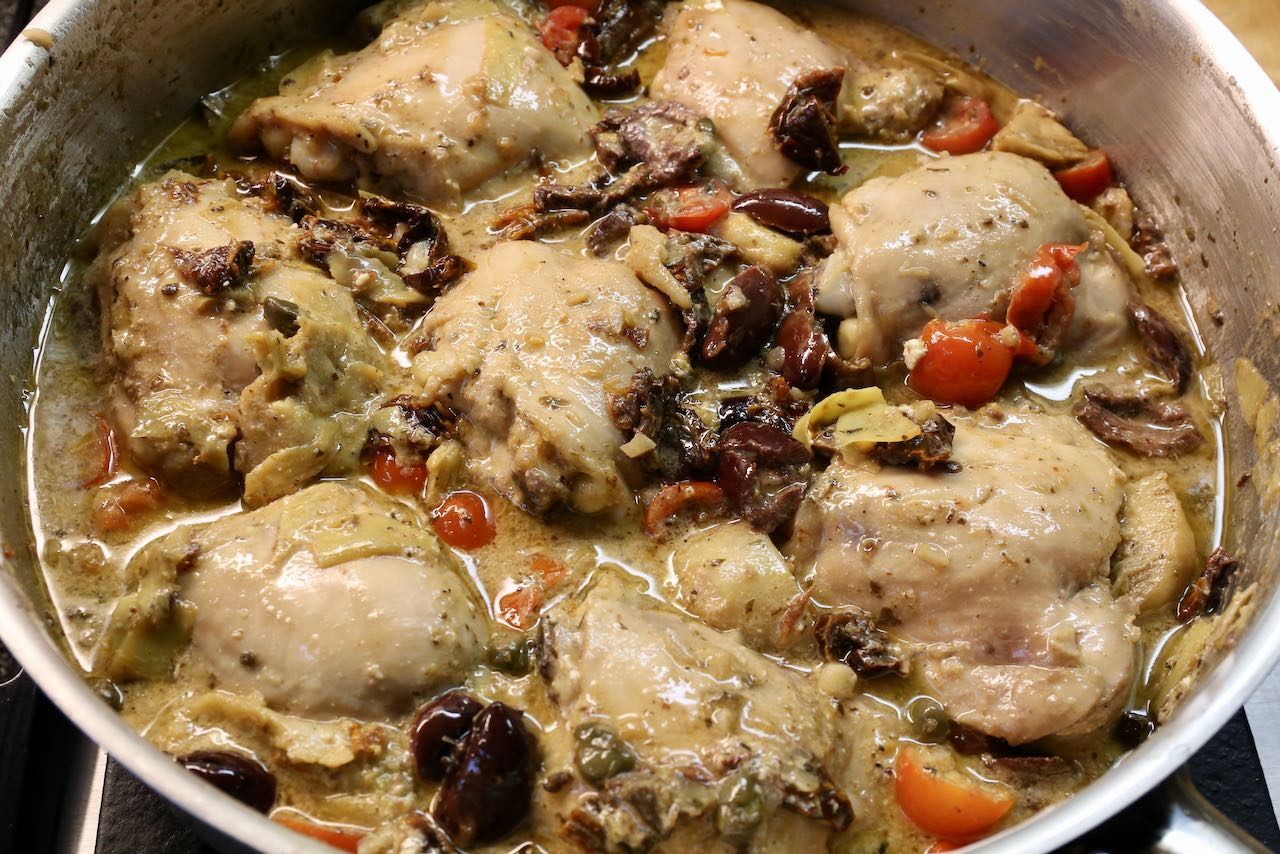 Baked chicken thighs cook over the stove with olives, sun-dried tomatoes, artichokes and capers.