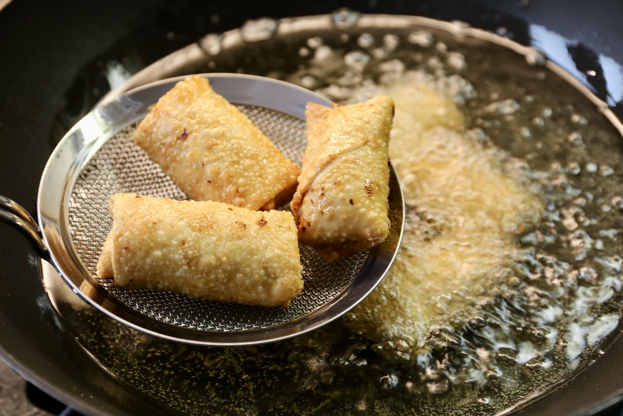 Use a metal sieve to remove crispy and browned Vietnamese Egg Rolls from hot deep fry oil.
