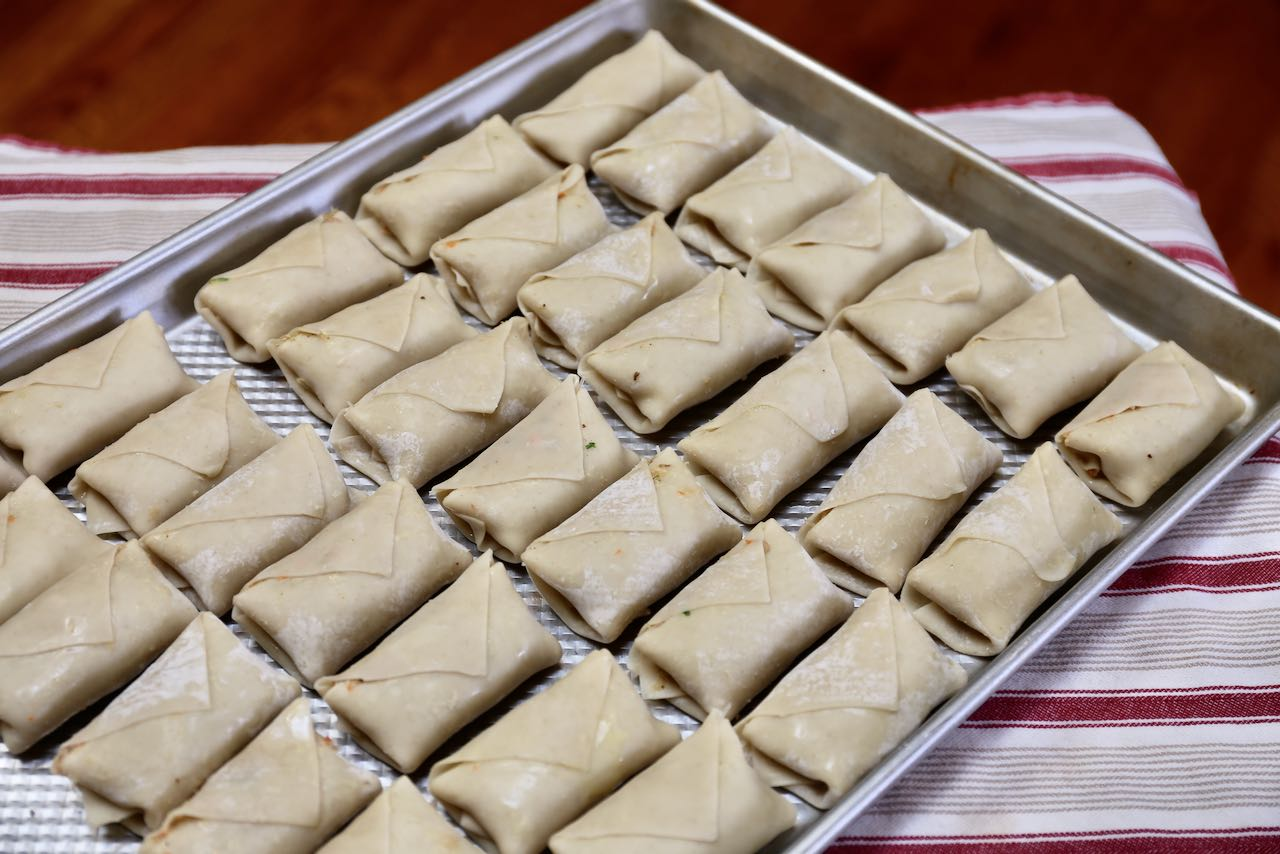Place folded and wrapped Vietnamese egg rolls on a baking sheet.