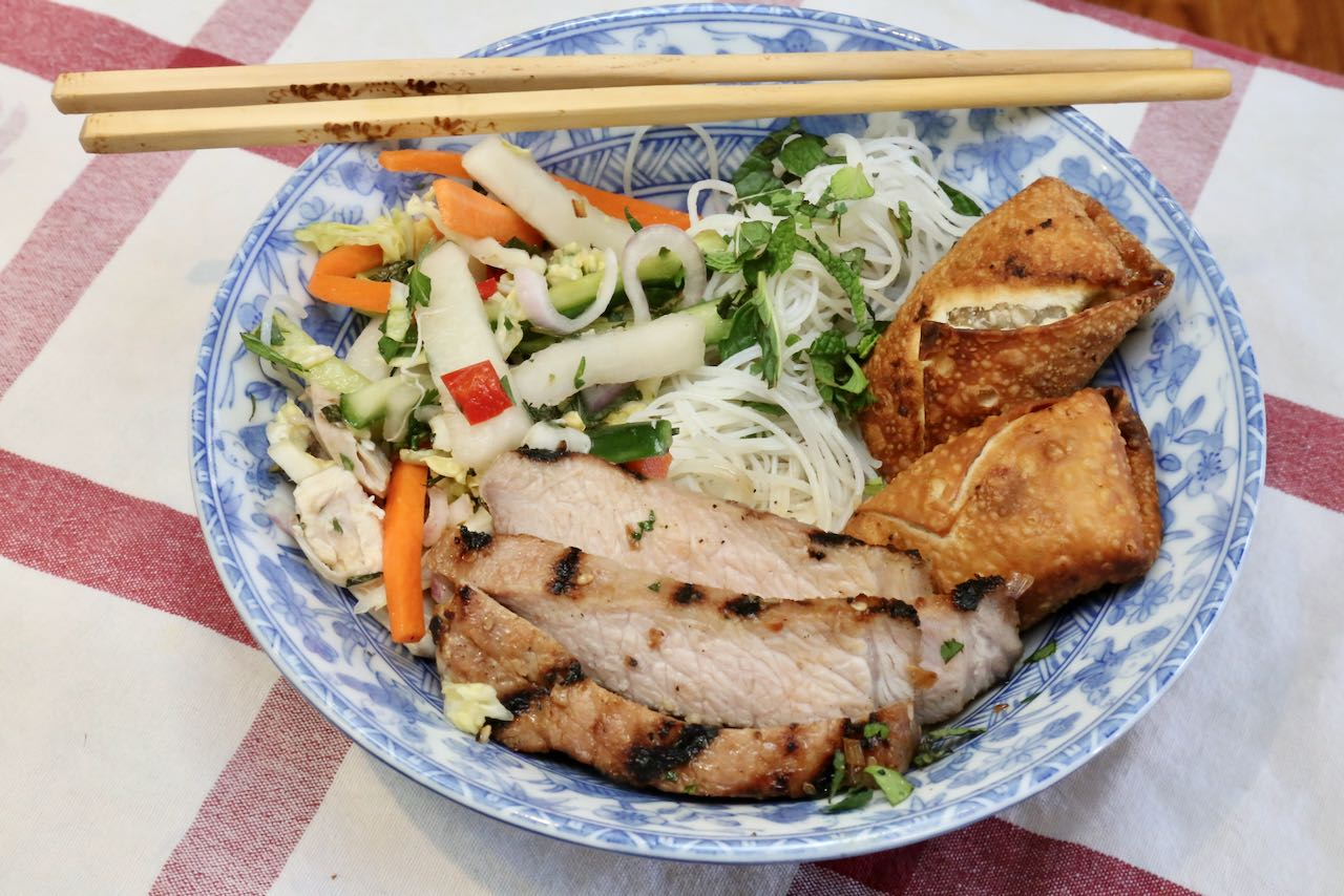 Serve Bun Thit Nuong with rice noodles, pickled vegetables and Vietnamese egg rolls.