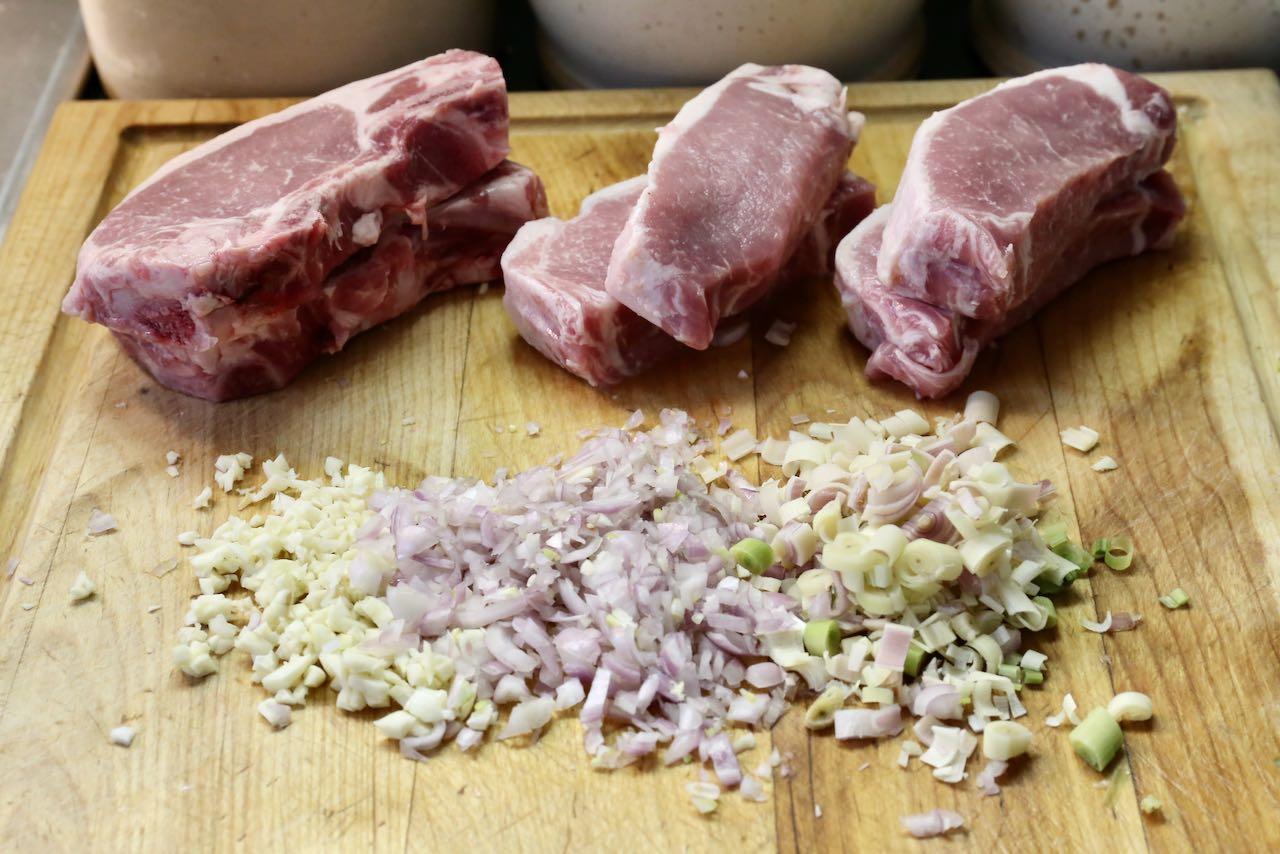 Bun Thi Nuong: Mince garlic, shallots and lemongrass. Trim excess fat off pork chops.
