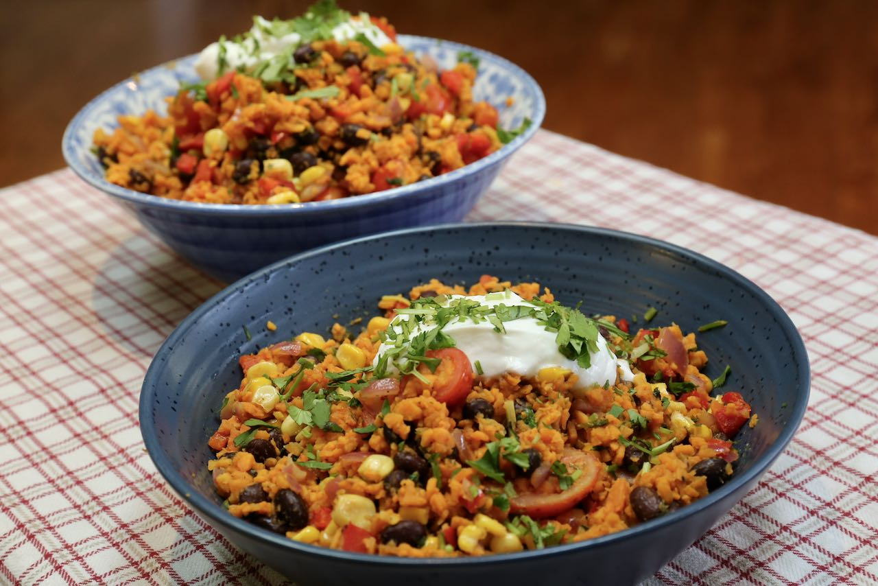 Serve sweet potato rice family-style topped with sour cream and chopped cilantro.