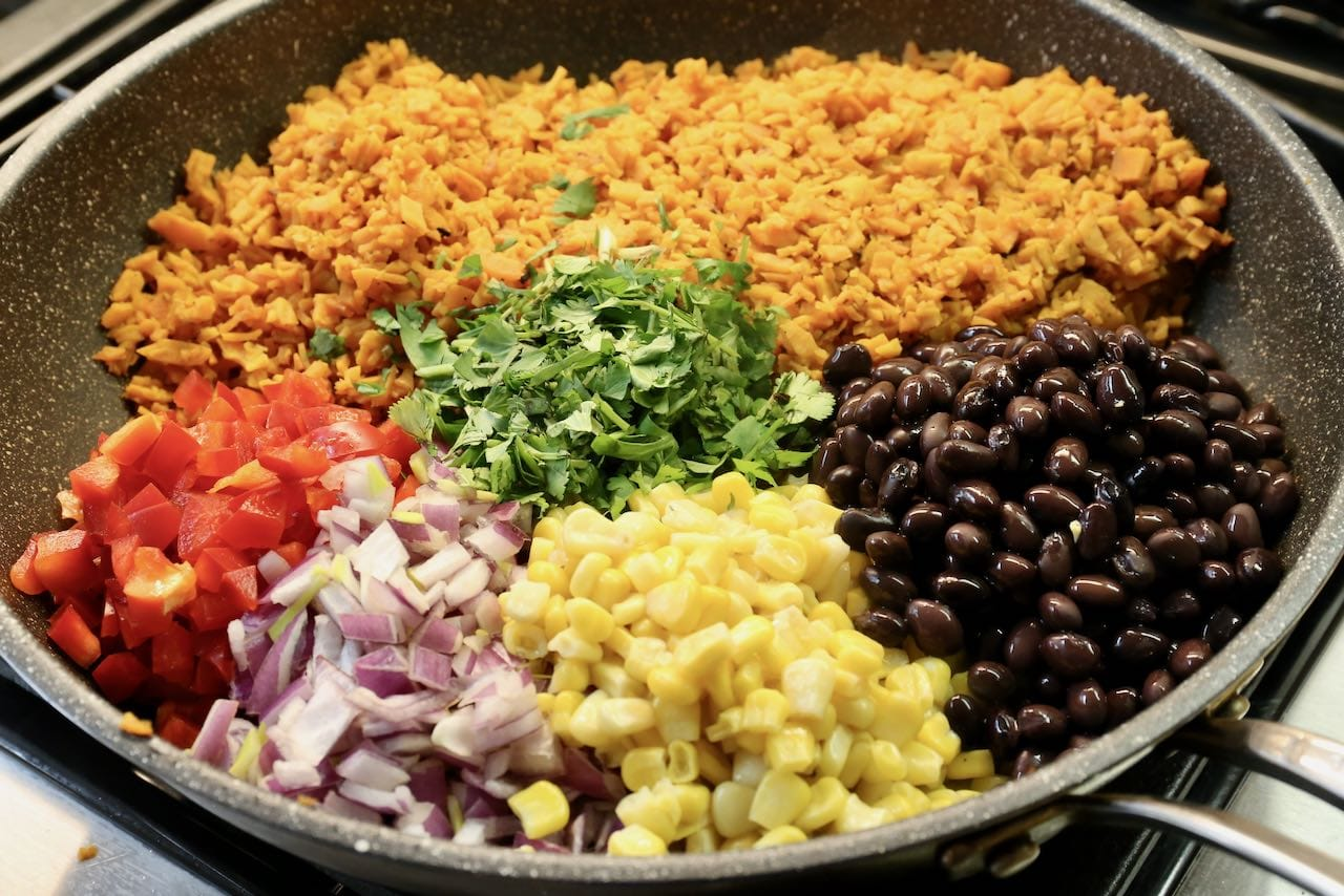 Prepare a Mexican dish by adding beans, corn, onion, peppers and cilantro.