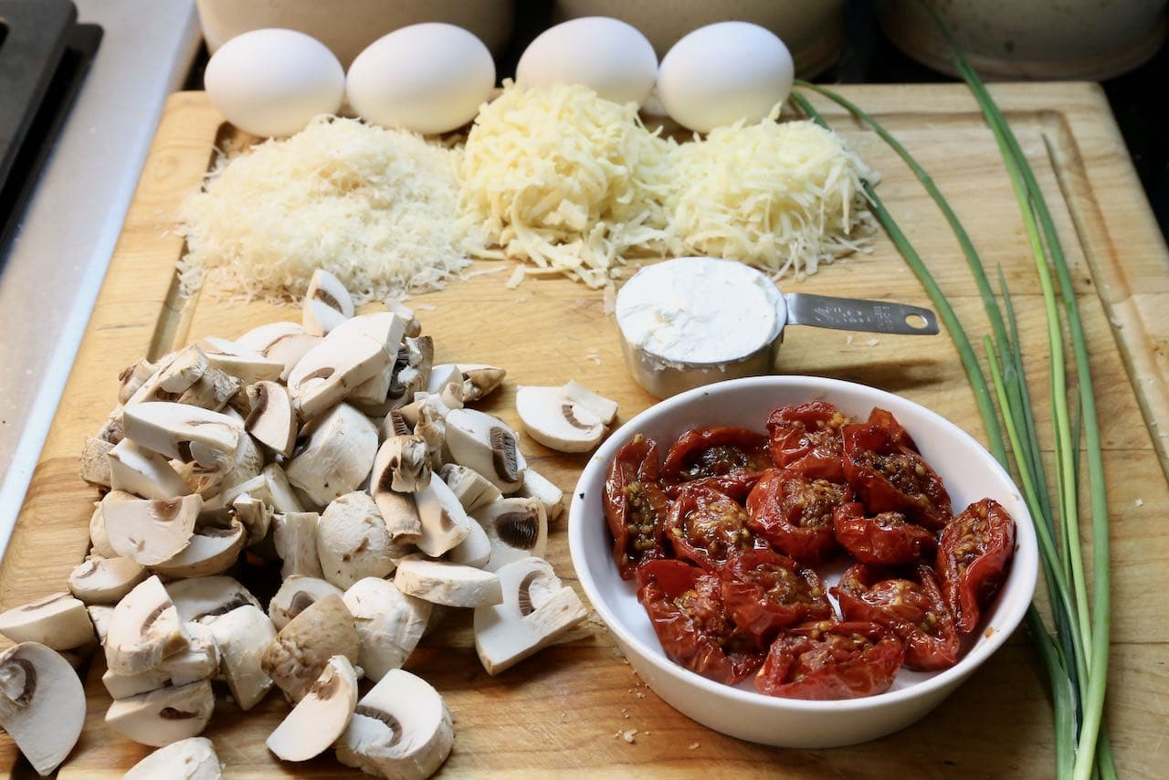 Breakfast Polenta features shredded cheeses, roasted tomatoes, mushrooms and fried eggs.