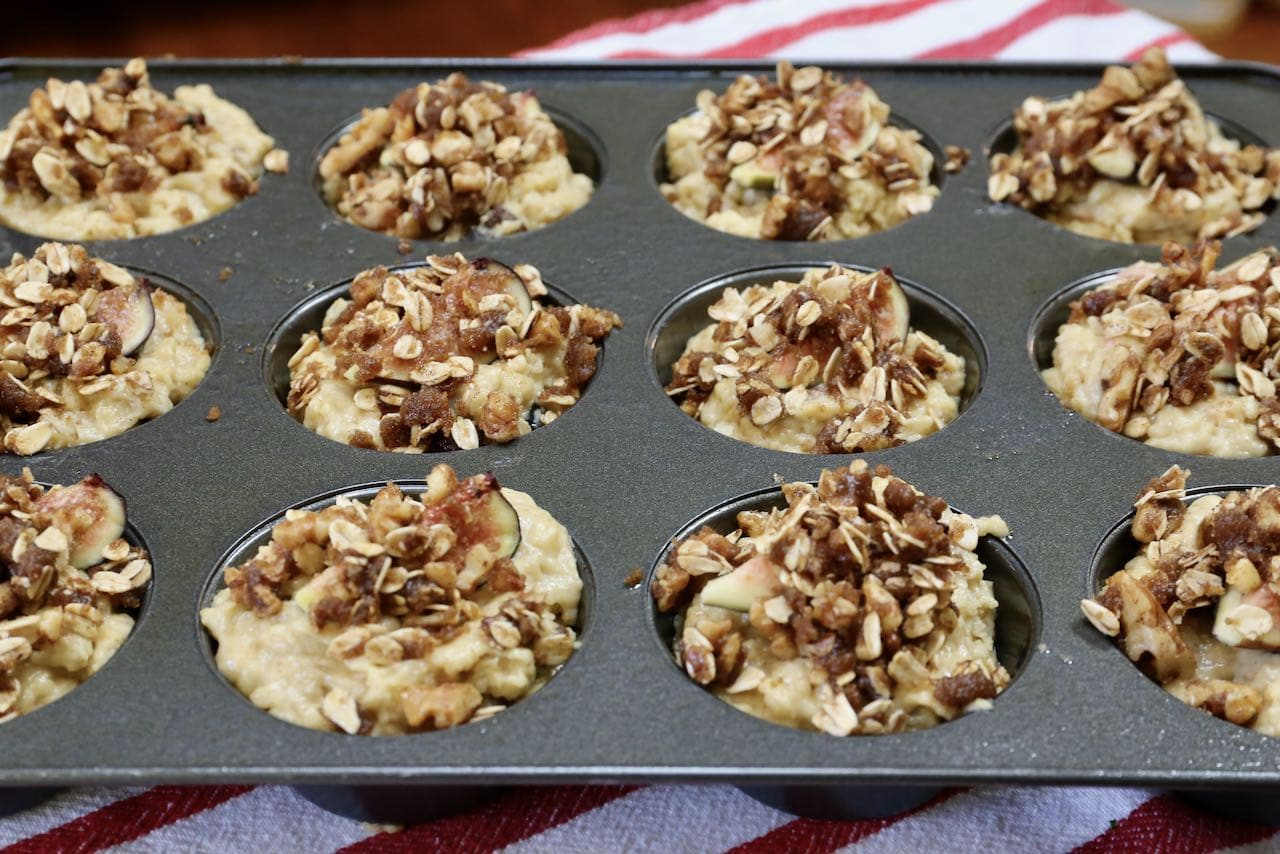 Top muffins with oat crumble before baking in the oven.