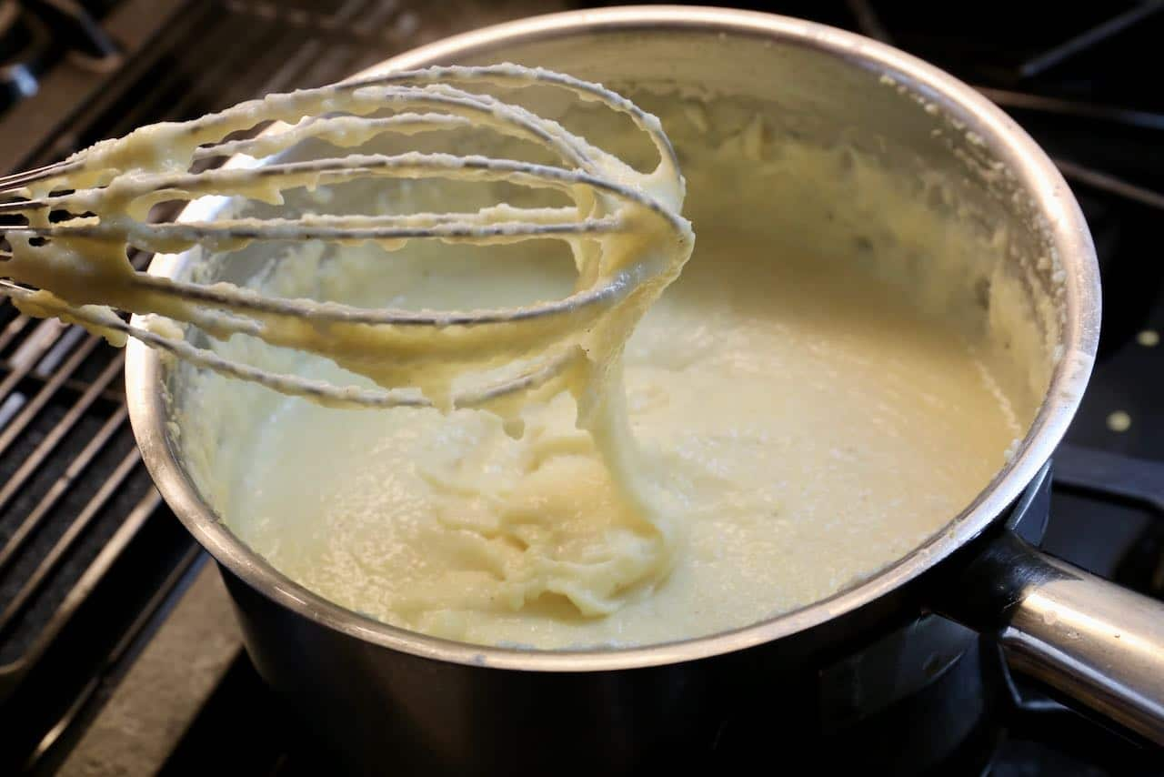 Constantly stir Cheesy Polenta with a whisky until creamy and smooth.