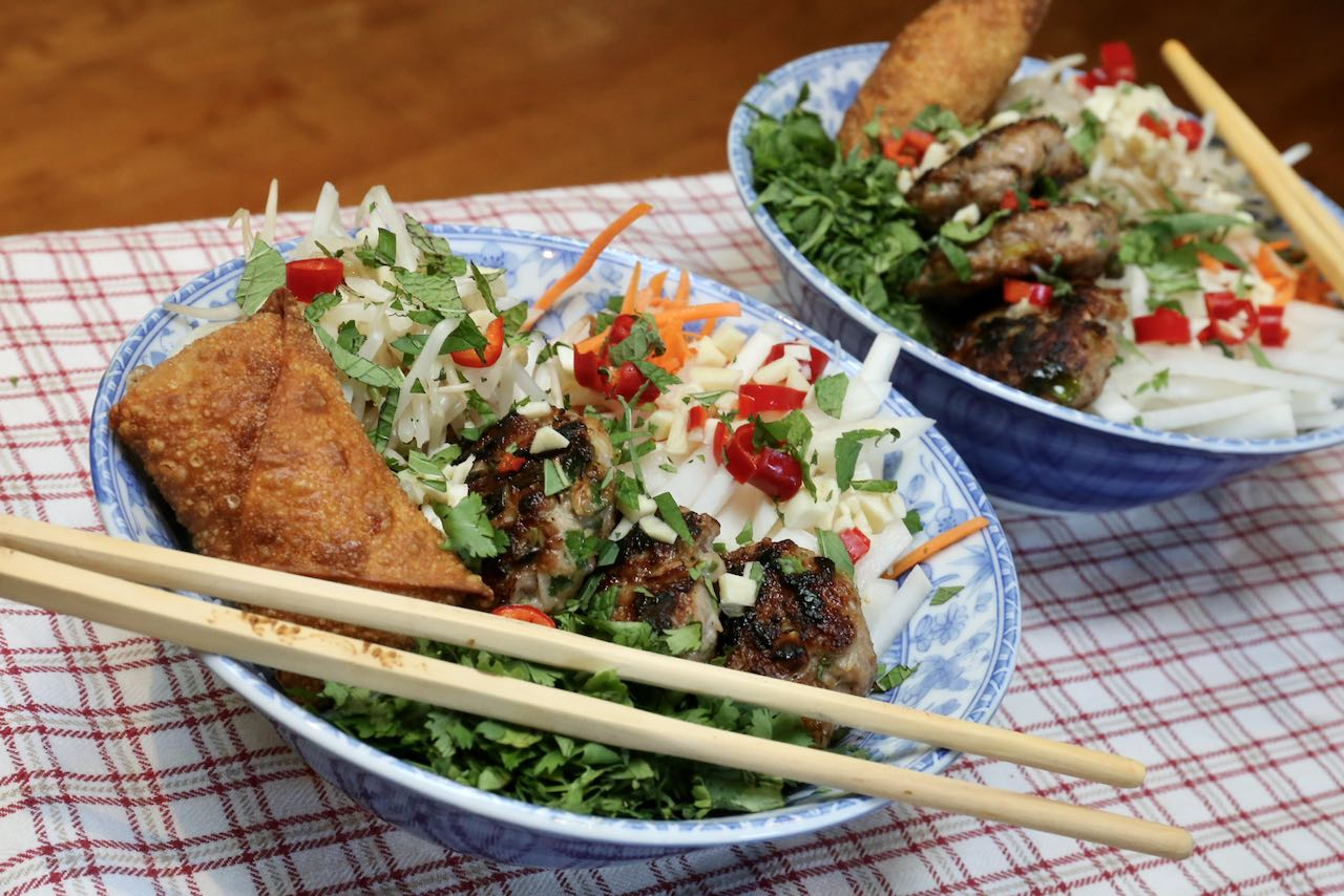 Top Bun Cha rice noodle bowls with chopped fresh herbs.
