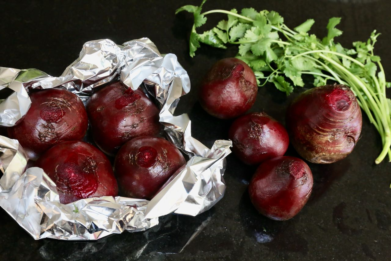 Roast beets wrapped in tin foil packages in the oven.