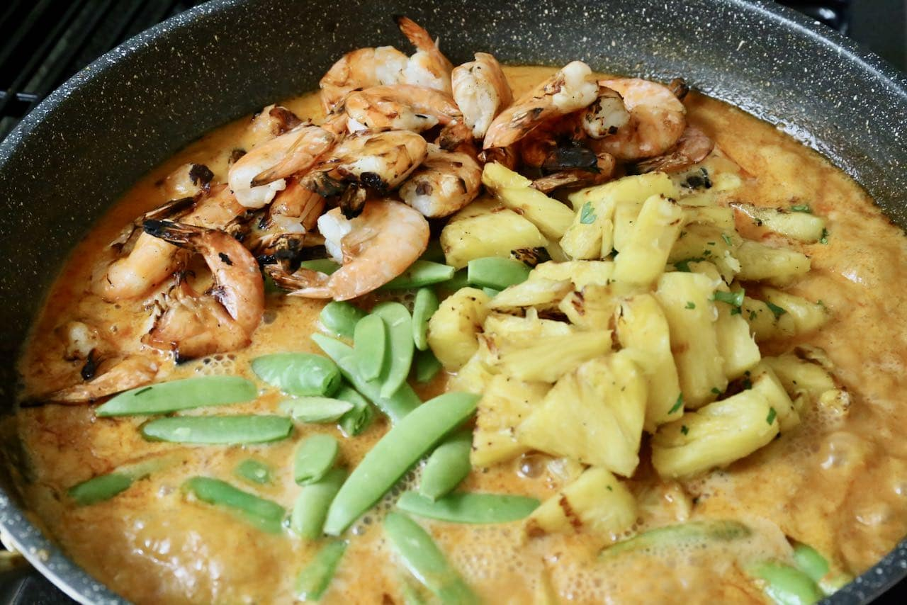 Add barbecued prawns, pineapple and snap peas to the Thai coconut cream sauce.