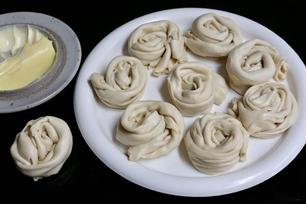 Wrap thin roti canai dough into spirals before flattening with the heel of your hand.